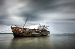 An old shipwreck boat abandoned stand on beach or Shipwrecked off the coast of Thailand.