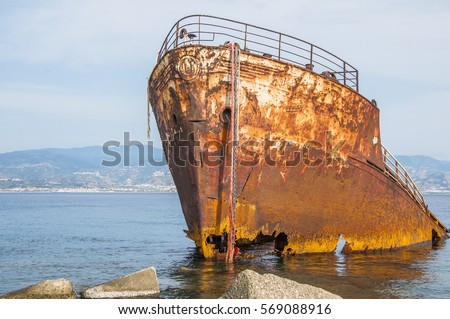 An old shipwreck or abandoned shipwreck. , Wrecked boat abandoned stand on beach or Shipwrecked off the coast of Messina, Sicily, Italy. #569088916
