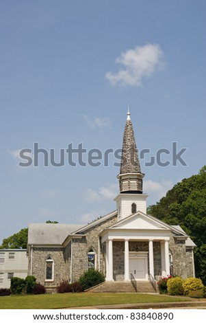 An old small stone church with a wood shingled steeple on a hill under blue skies