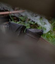 An old smoking smoker. A smoker hangs on the hive's body and smokes. An old smoker.