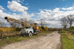 An old Soviet truck crane stands on the side of a village road