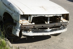 An old sprawled rusty white passenger car abandoned in a public parking lot. Car trash.