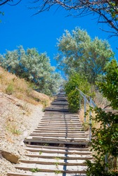An old staircase uphill between trees in hot weather under the scorching sun.