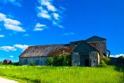 an old stone abandoned building against a blue sky, with a green meadow and a road in the foreground