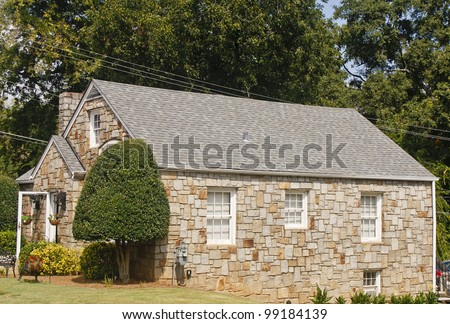 An old stone building with grey shingle roof - stock photo