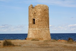 An old stone tower on the beach, in Italy.
