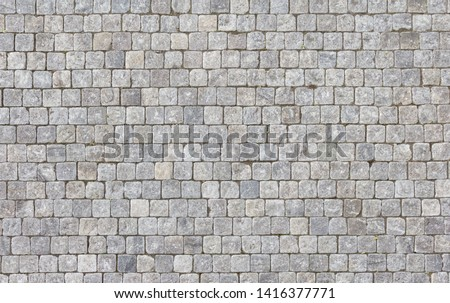 An old stoneblock pavement cobbled with square granite blocks.