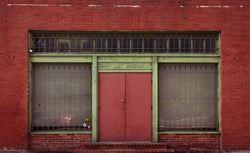An old storefront on the side of a red brick building