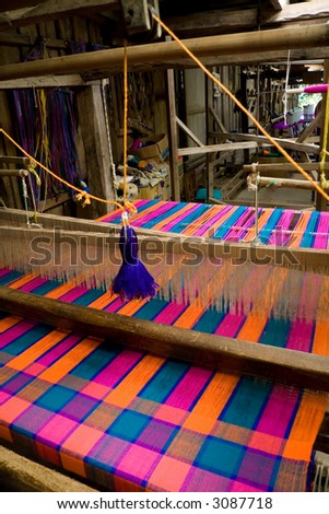 An old-style loom producing a colorful cloth