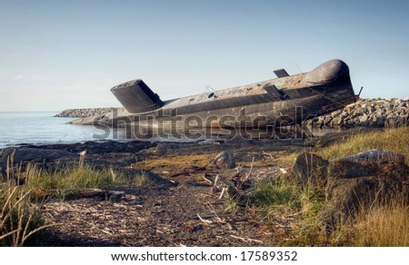 An old submarine leaning by the back in the water