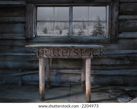 An old table sits in front of a window in an abandoned cabin in the winter.