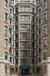 An old tall building in Manhatan, New York, with a symmetrical pattern on a sunny summer day with a warm atmosphere.