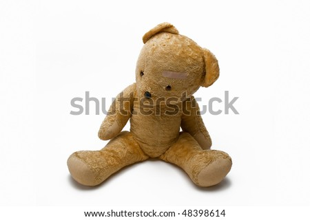 An Old Teddy Bear With Sticking Plaster Isolated On White Background