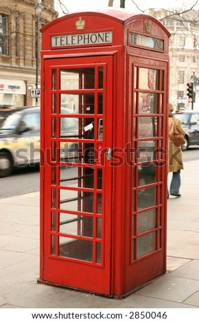 an old telephone box in London, with a london taxi in the background with motion blur on the taxi