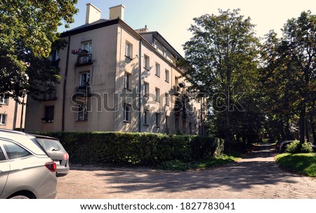 An old tenement house in the Szydłówek housing estate and the road and parked cars