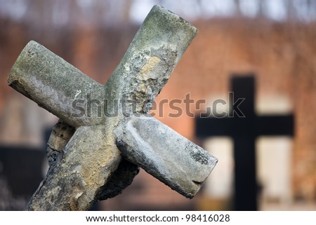 An old 19th century leaning gravestone cross at cemetery, blurred background, shallow depth of field composition