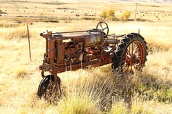 An old three wheel tractor sits next to a large cattle ranch in northern California