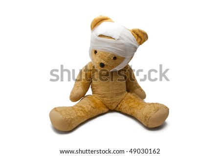 An Old Toy Bear With Bandage Isolated On White Background
