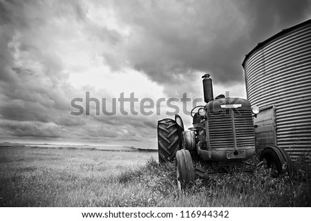 An old tractor standing next to a silo at canadian badlands in Drumheller, Alberta