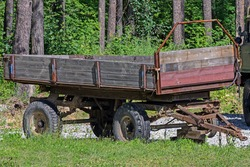 An old tractor trailer is parked on a rural street