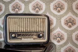 An old transistor radio, with knobs and buttons for manual tuning. In the background a vintage wallpaper. Ancient object, worn and ruined by time.