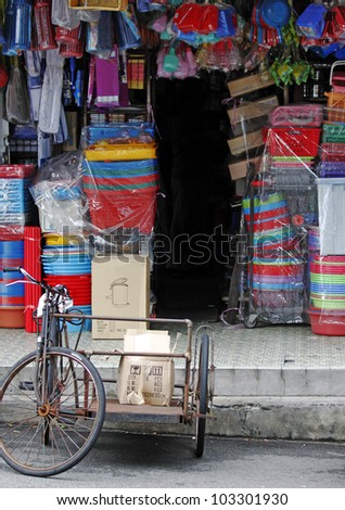 An old tricycle delivery transportation at a traditional sundry shop selling colorful household wares in Petaling Jaya, Malaysia.