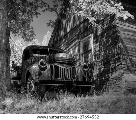 An old truck abandoned close by a cottage.