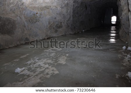 An old tunnel with a floor of ice excavated in the stone during the first global war, in the North of italian Alps