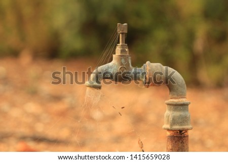 An old, un used tap with cobwebs in the outdoors.