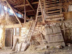 An old village building built of stone and wood, in which cattle are housed on the ground floor, and hay is stored in the room above.