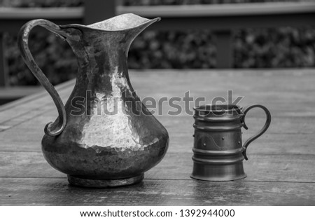 An Old Vintage Copper Pitcher and Pewter Mug Shot in Black and White #1392944000