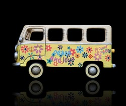 An old vintage hippie peace and love van over a black background
