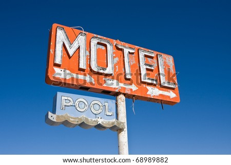 An old vintage, neon sign points to a motel that was never built.