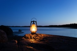 An old vintage oil lantern on a rock by the sea. Evening time. Beautiful colorful illuminated lamp. Chillout travel concept.