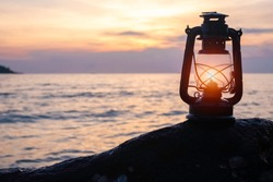 An old vintage oil lantern placing on a rock by the sea. It's evening time, the sun is setting. This is so romantic yet lonely scenery. The lamplight is used by fisherman. Chillout travel concept.
