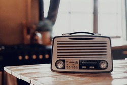 an old vintage radio receiver sits on a wooden table. stylish old kitchen morning in the village and daylight from the window. copy space