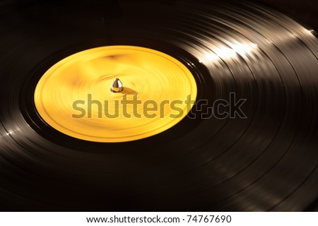 An old vinyl LP playing on a turntable. Good background for music designs.