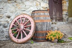 an old wagon wheel, a wooden barrel and a pot with flowers