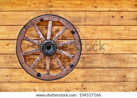 An old wagon wheel decorated with a wooden wall