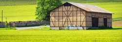 An old warehouse in Rhine valley, Germany. Green plowed field in the background. Panoramic view. Idyllic rural scene. Traditional architecture, agriculture, farm and food industry