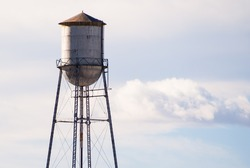 An old water tower standing in a rural town with the moon on the left.