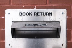 An old, weathered, aged metal book return container in a brick wall in downtown London. Reading books during the COVID-19 pandemic, high-volume checkouts and holds.