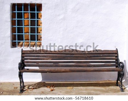 An old weathered wooden bench against a white washed wall on the Greek island of Crete.