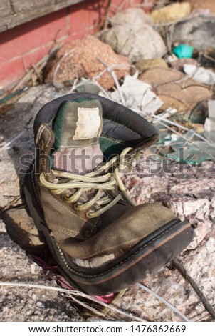 An old, weathering hiking boot left in a vacant lot  #1476362669