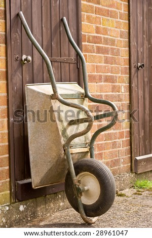 an old well used and worn wheel barrow propped against a wooden shed door.
