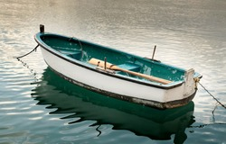 An old white and turquoise wooden rowing boat is empty at mooring in the azure waters of the Mediterranean sea. It is a typical example of the small boats found on the coast of Malta.