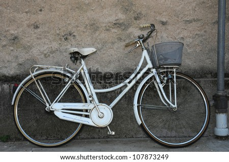 an old white bicycle leaning against a house wall