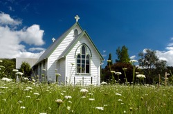An old white church in a field full of spring white flowers in Kawakawa Northland New Zealand.No people. Copy space