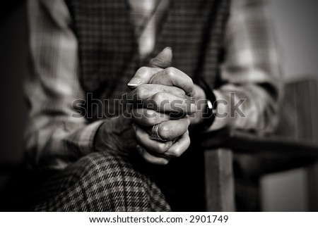 An old widow is praying while mourning her late husband