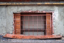 An old window covered with iron bars minus the first floor of a residential building of the sixties of the twentieth century
